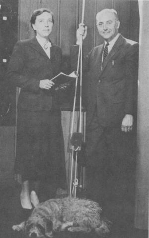 Black and white photo of Daniel and Catherine Dewey standing over their pet dog.