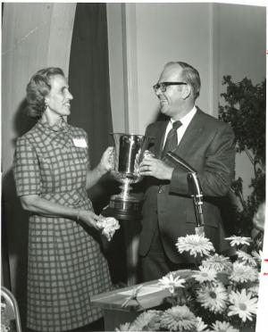 Black and white photo of Kay Bradley and Art O'Leary holding a large award.
