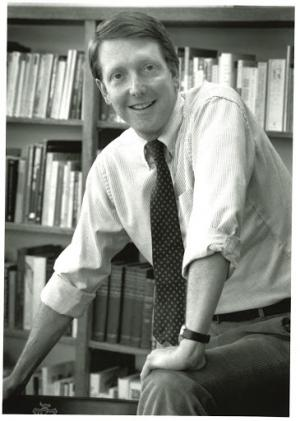 Black and white photo of Paul Chapman standing in front of a book case.